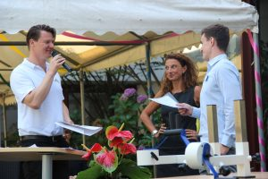 Florian Winger spricht in ein Mikrofon, im Vordergrund steht ein Plaudertisch
