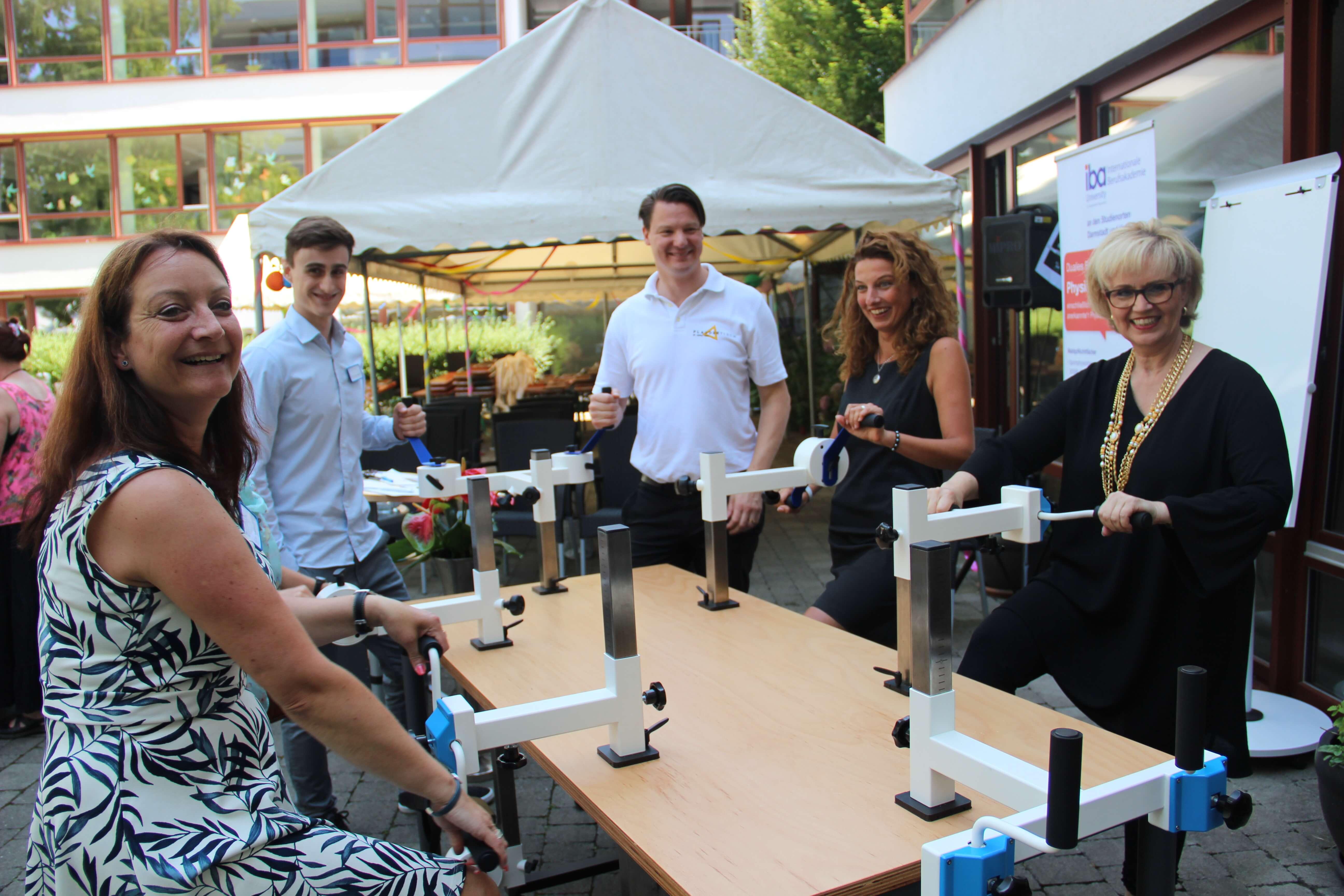 Florian Winger und Mitarbeiter von Agaplesion und iba stehen gut gelaunt an einem Plaudertisch