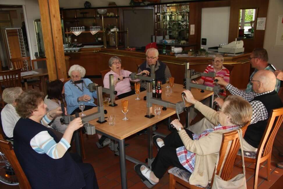 Eine Gruppe älterer Menschen sitzt um einen Plaudertisch und übt.