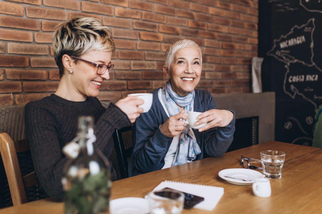 Zwei lächelnde Frauen sitzen an einem Tisch im Café