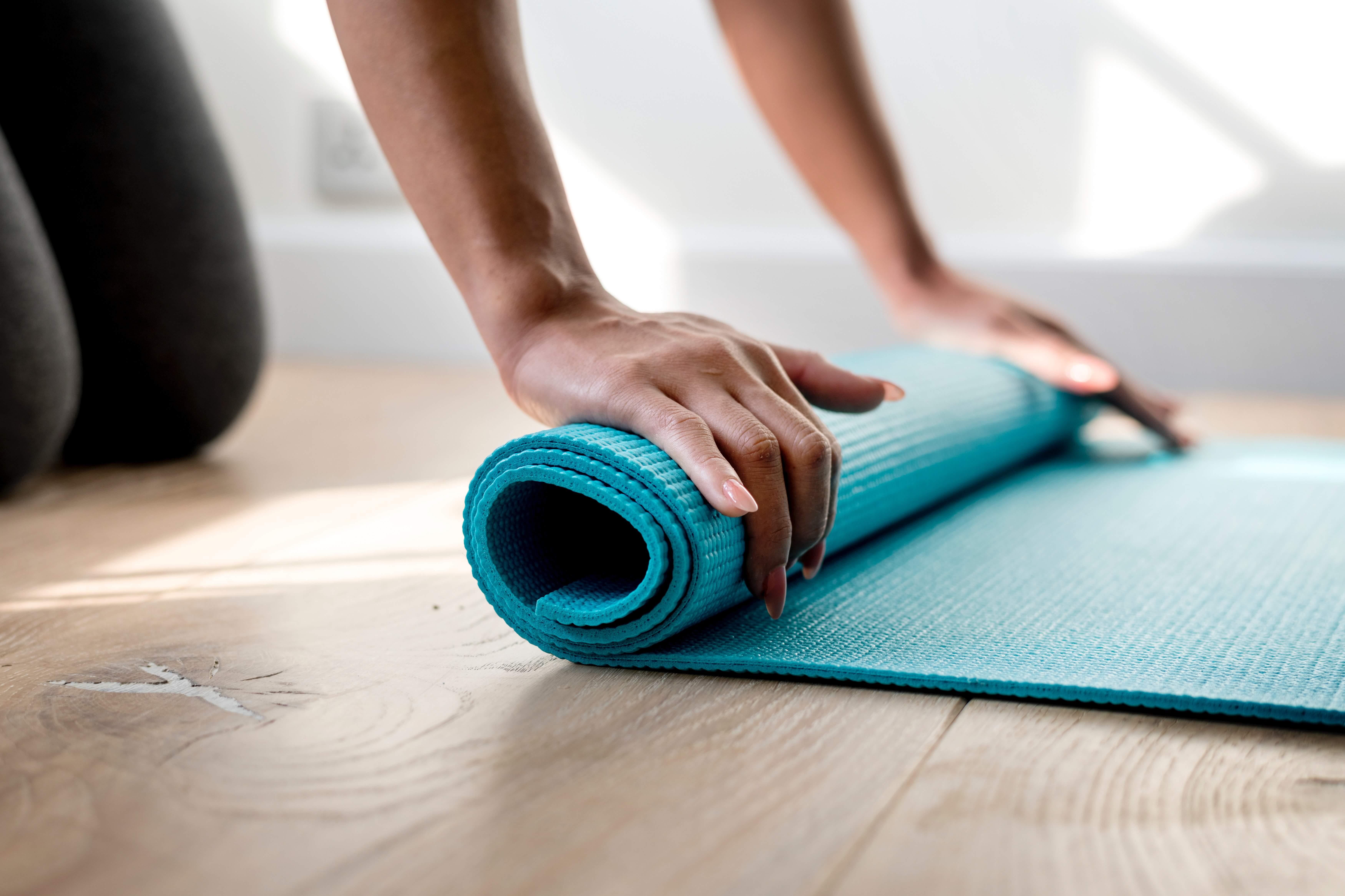 Frau rollt eine Yoga-Matte auf dem Boden aus