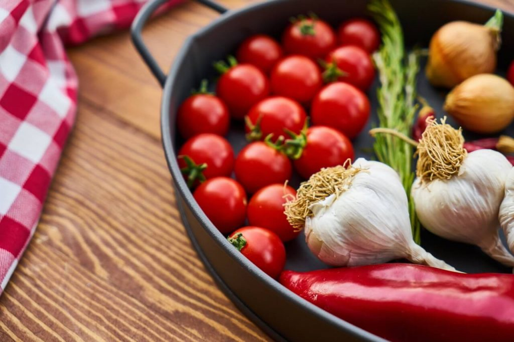 Topf mit Tomaten, Paprika, Knoblauch, Zwiebeln und Kräutern