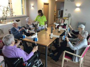 Ältere Menschen sitzen in Pflegeheim lächelnd am Plaudertisch