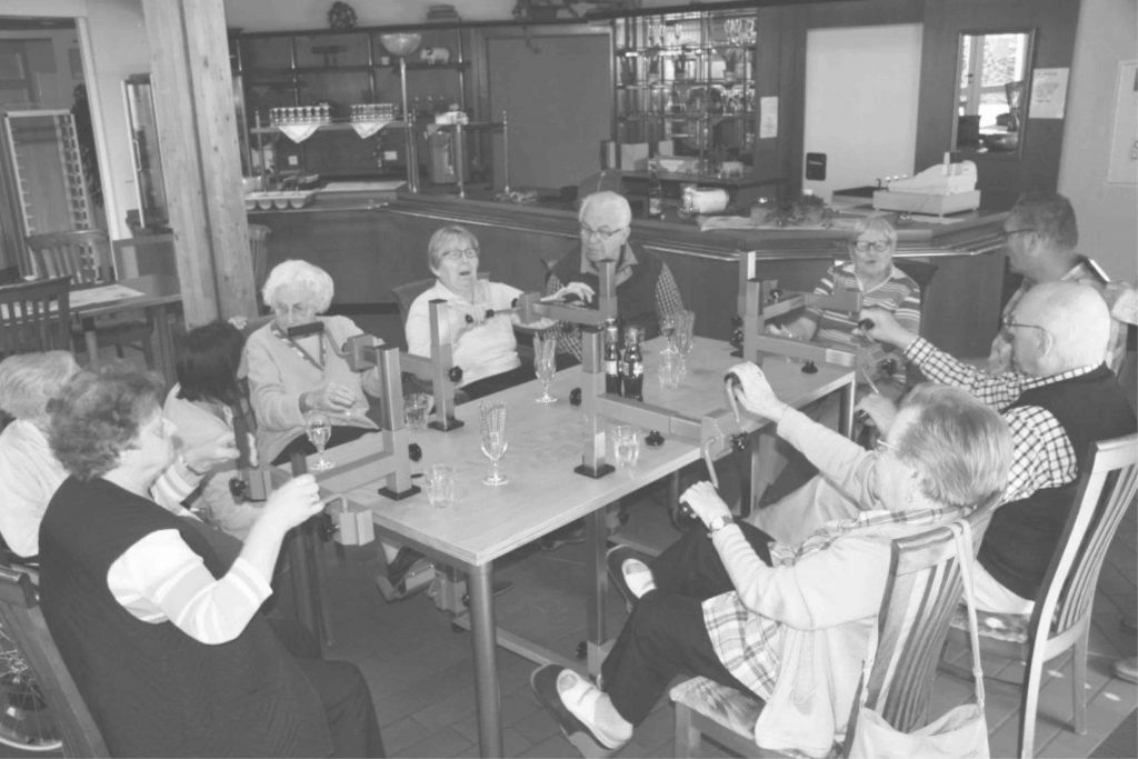 Schwarz-Weiß-Foto von älteren Menschen am Plaudertisch