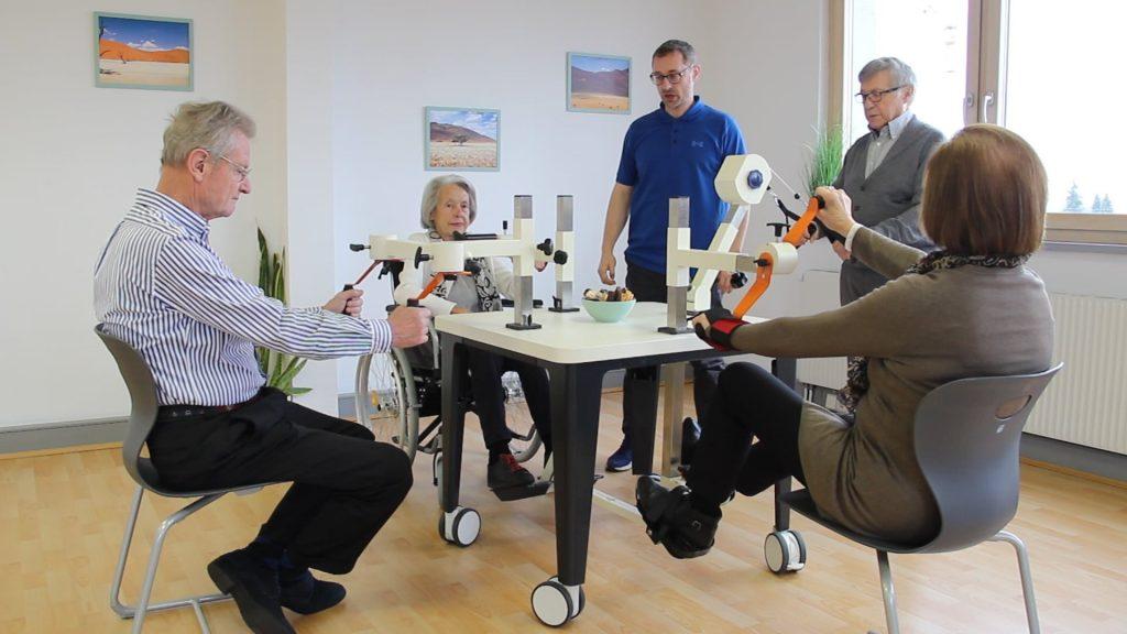 Bildausschnitt aus einem Video, in dem vier Personen am Plaudertisch Rechenaufgaben lösen