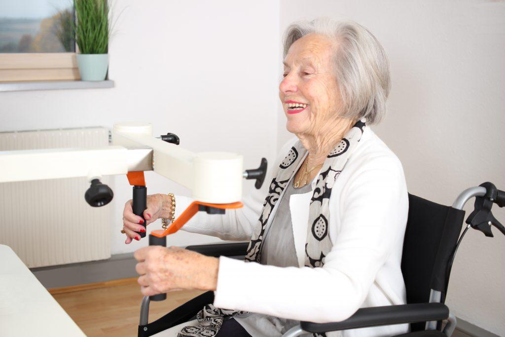 Eine ältere Frau im Rollstuhl sitzt am Plaudertisch und bewegt sich lächelnd am Kaffemühle-Übungsgerät