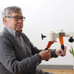 Älterer Mann sitzt am Übungsgerät Kaffeemühle und schaut verschmitzt