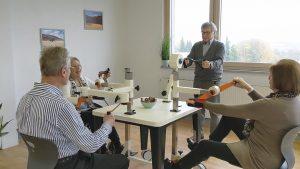 Mehrere Senioren sitzen und stehen am Plaudertisch und trainieren