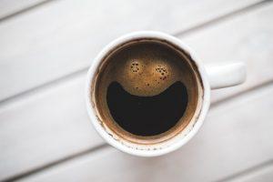 Kaffeetasse von oben mit Schaum in Form eines lachenden Smileys.