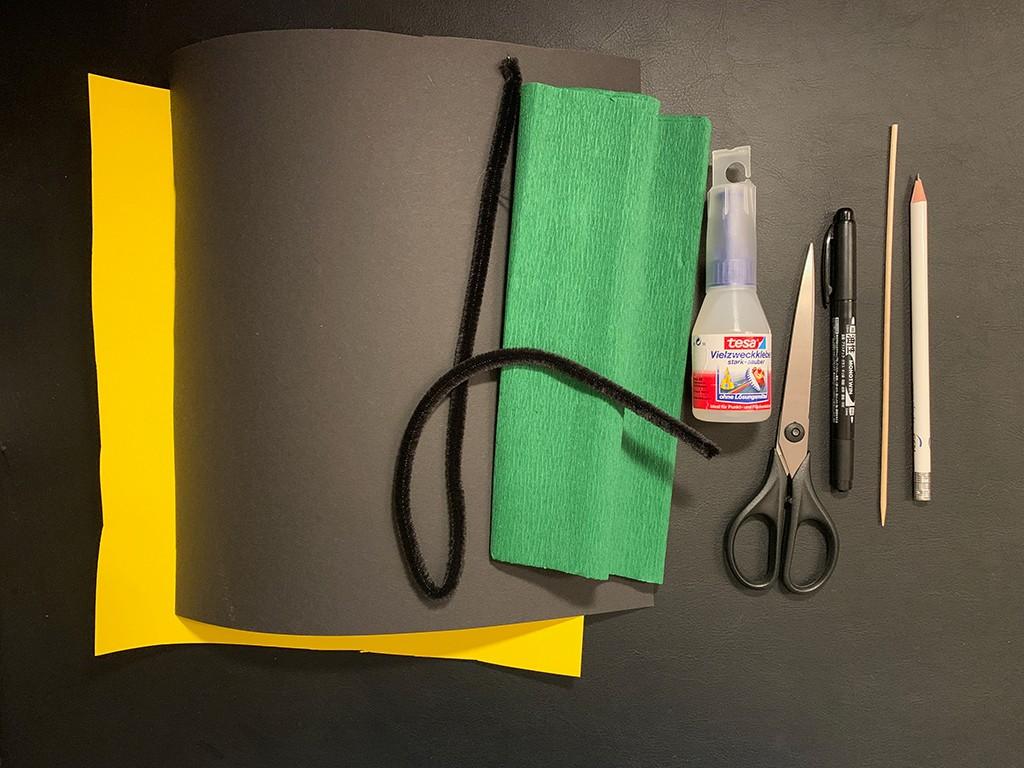Bastelmaterial um eine Biene mit Senioren zu basteln: Gelber und schwarzer Karton, Kreppband, Pfeifenputzer, grünes Kreppband, Klebstoff, Schere, Schaschlikspieß und Stifte