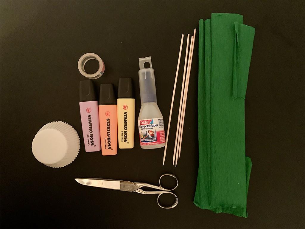 Bastelmaterial für Papierblumen: Muffinförmchen, Text-Marker, Schaschlikspieße, grünes Kreppband, eine Schere und Tesafilm