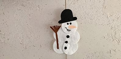 Schneemann aus Wattepads an einer Girlande vor einer Fassadenwand
