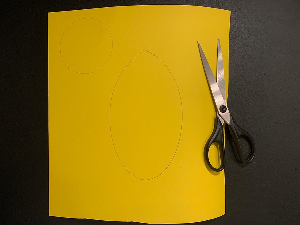Gelber Tonkarton mit aufgezeichneten Umrissen für Körper und Kopf der Biene auf dem eine Schere liegt