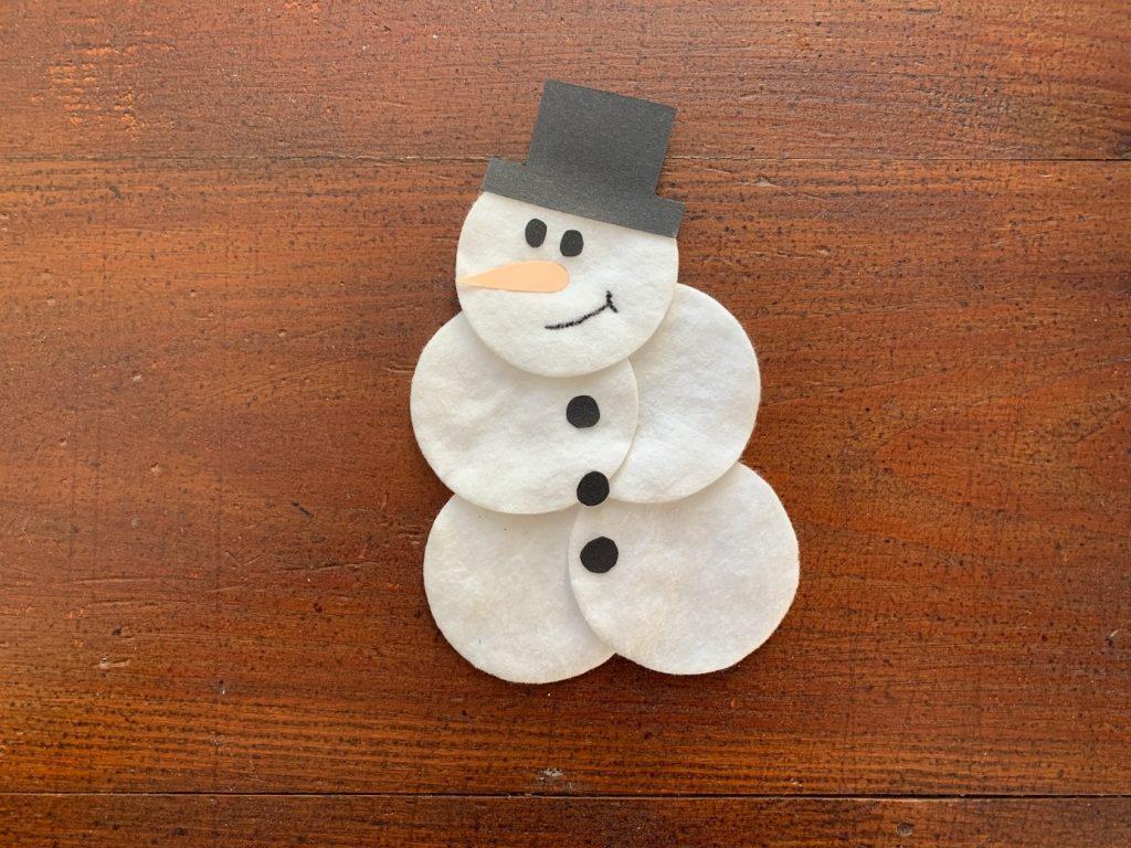 Lachender Schneemann aus Wattepads mit Hut, Nase und Knöpfen aus ausgeschnittenem Papier