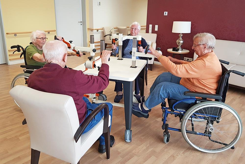 Vier Senioren bewegen sich am Plaudertisch, zwei Frauen sitzen dabei im Rollstuhl
