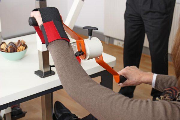 Blick über die Schulter einer Seniorin am Plaudertisch auf die Hände an der Drehorgel. Eine Hand ist mit einem roten Handfix-Handschuh am Griff fixiert.