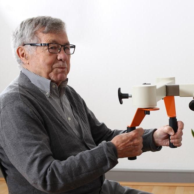 Seitliches Foto von einem Senioren der verschmitzt lacht und die Griffe der Kaffeemühle des Plaudertischs hält.