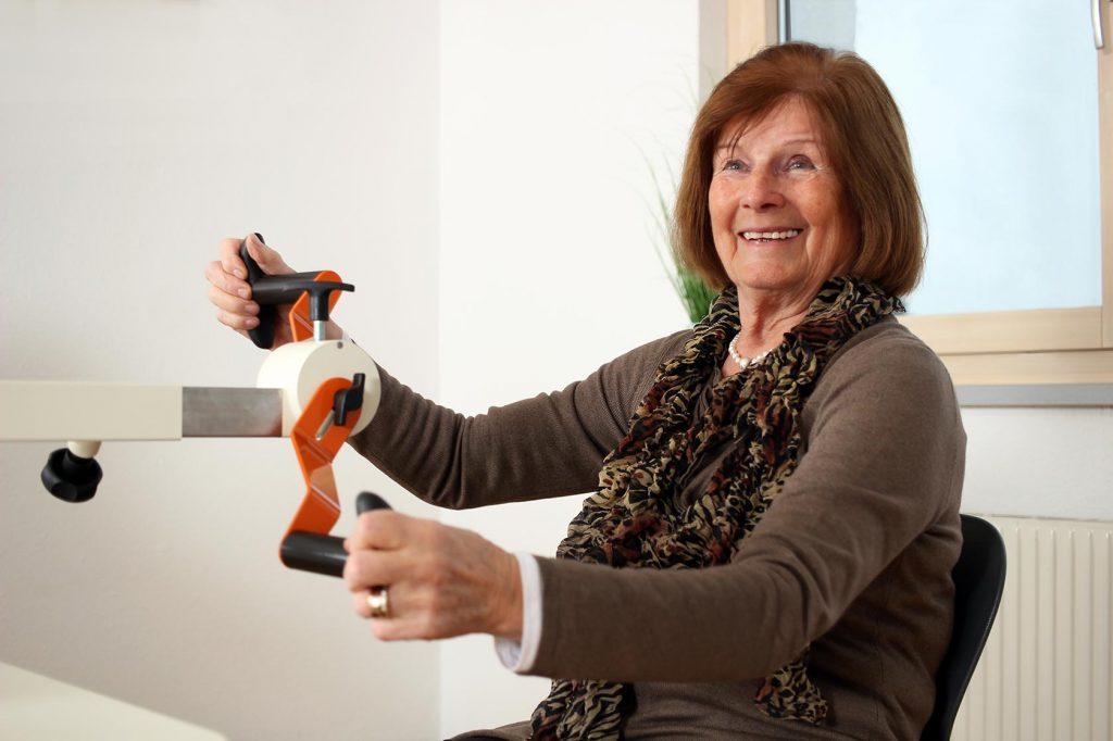 Foto einer Seniorin in braun, die lachend an der Drehorgel trainiert.