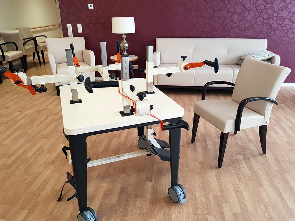 Plaudertisch im Aufenthaltsraum einer Pflegeeinrichtung mit cremefarbenen Sitzmöbeln und einer lila Wand.