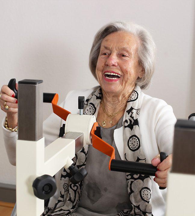 Senorin in weiß-grau sitzt lachend an der Drehorgel des Plaudertischs und hält die Griffe in den Händen