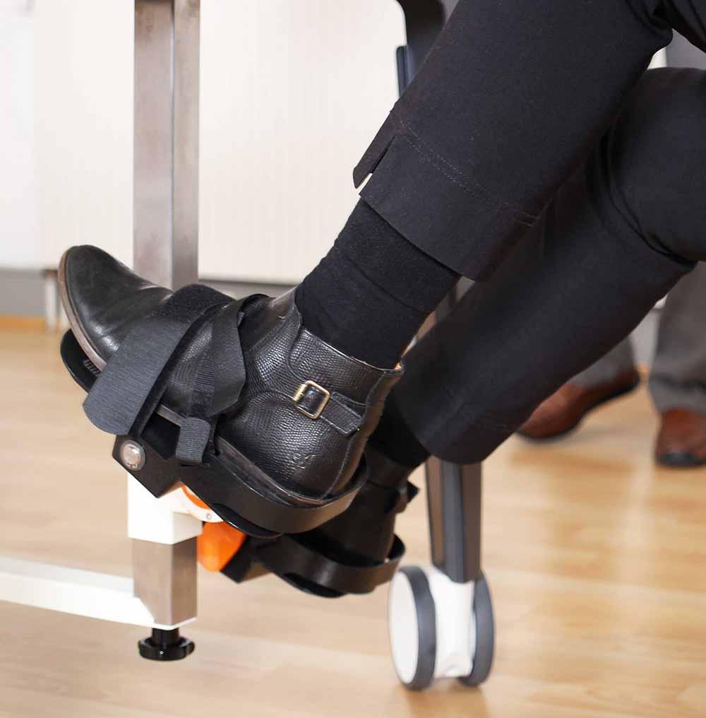 Füße einer Seniorin, die in die Pedale des Fahrrads am Plaudertisch tritt.