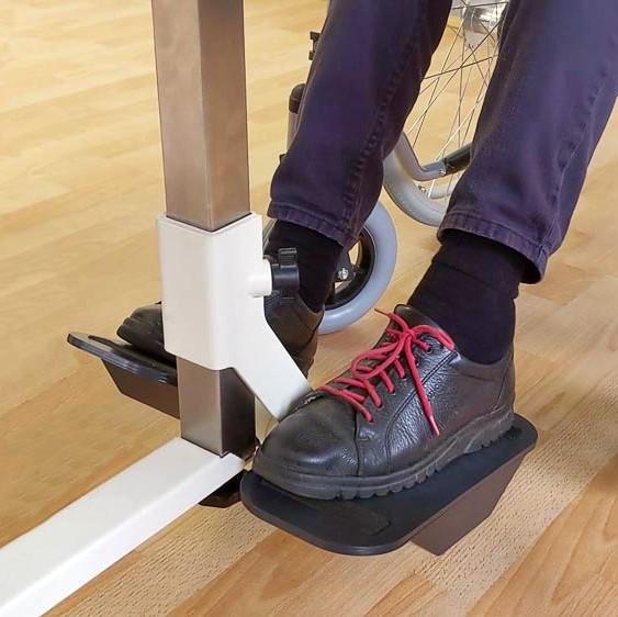 Füße in schwarzen Schuhen einer Frau im Rollstuhl stehen auf der Plaudertisch-Nähmaschine